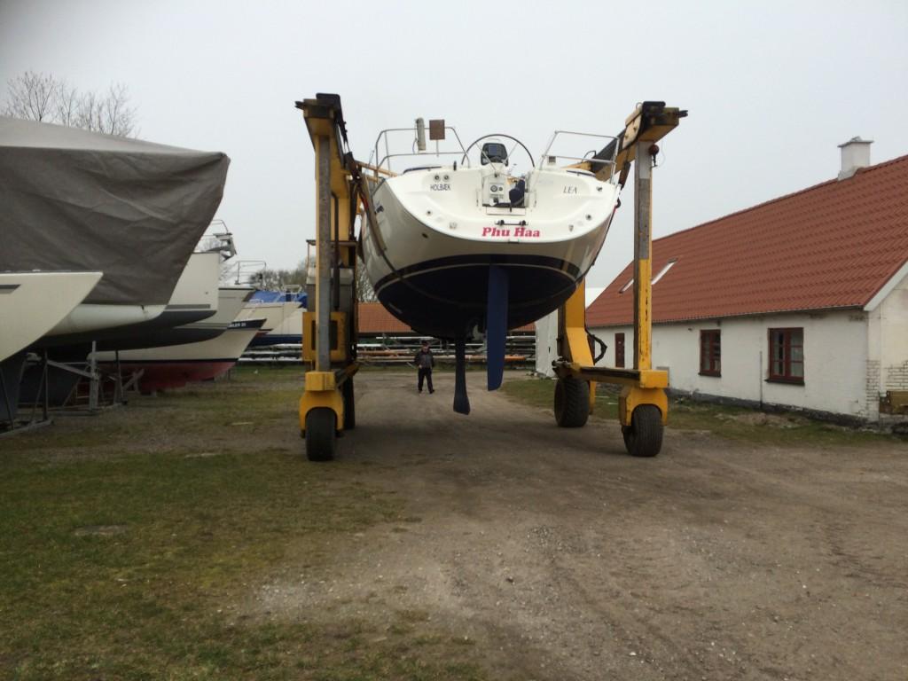 Havnens kran kan lige netop køre afsted med båden.